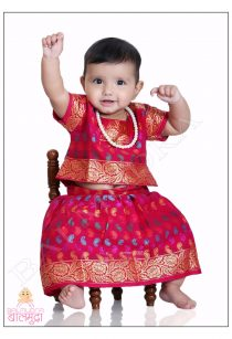 Cute little girl in Red Colour traditional dress sitting on a Chair