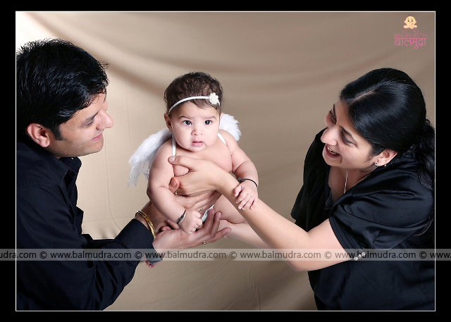 Four months old baby. Mother father daughter photo ,Photo Shoot done by , Shrikrishna Paranjpe , Balmudra Studio , Pune , 9822284771 , www.balmudra.com