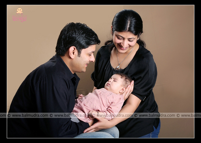 Indian Mother and father smiling at sleeping baby girl ,Photo Shoot done by , Shrikrishna Paranjpe , Balmudra Studio - Pune - 9822284771 - www.balmudra.com